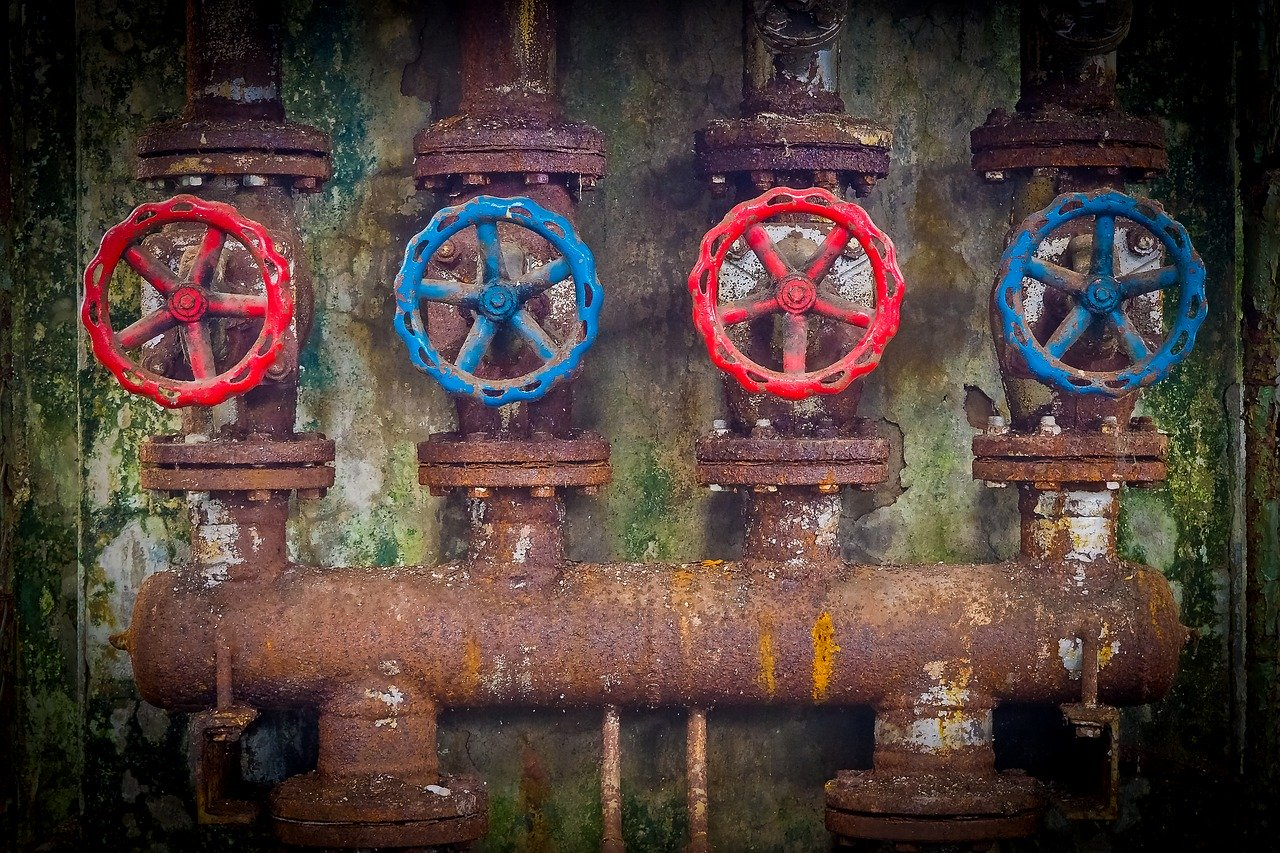 red and blue valve wheels on a rusty pipeline